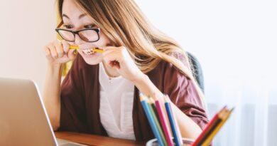 femme devant un ordi qui mâche une crayon